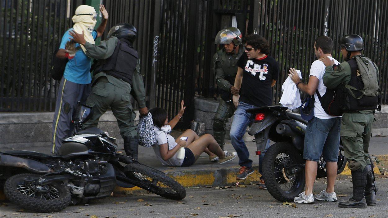 Des membres de la Garde nationale du Vénézuéla arrêtent des manifestants qui soutiennent l'opposition, lundi à Caracas.