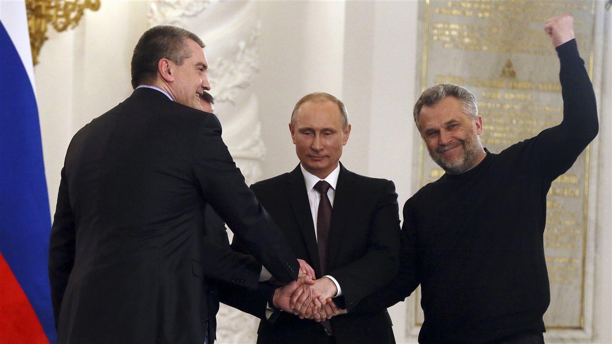 Le prédisent russe, Vladimkir Poutine, scelle par une poignée de main l'accord sur l'annexion de la Crimée avec les premier ministre de Crimée, Sergeï Aksyonov (gauche) et le maire de Sébastopol, Alexei Chaliy (droite).