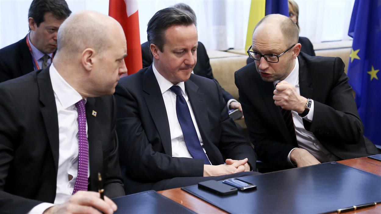 Le premier ministre par intérim de l'Ukraine, Arseni Iatseniouk (droite), discute avec ses homologues britannique et suédois.