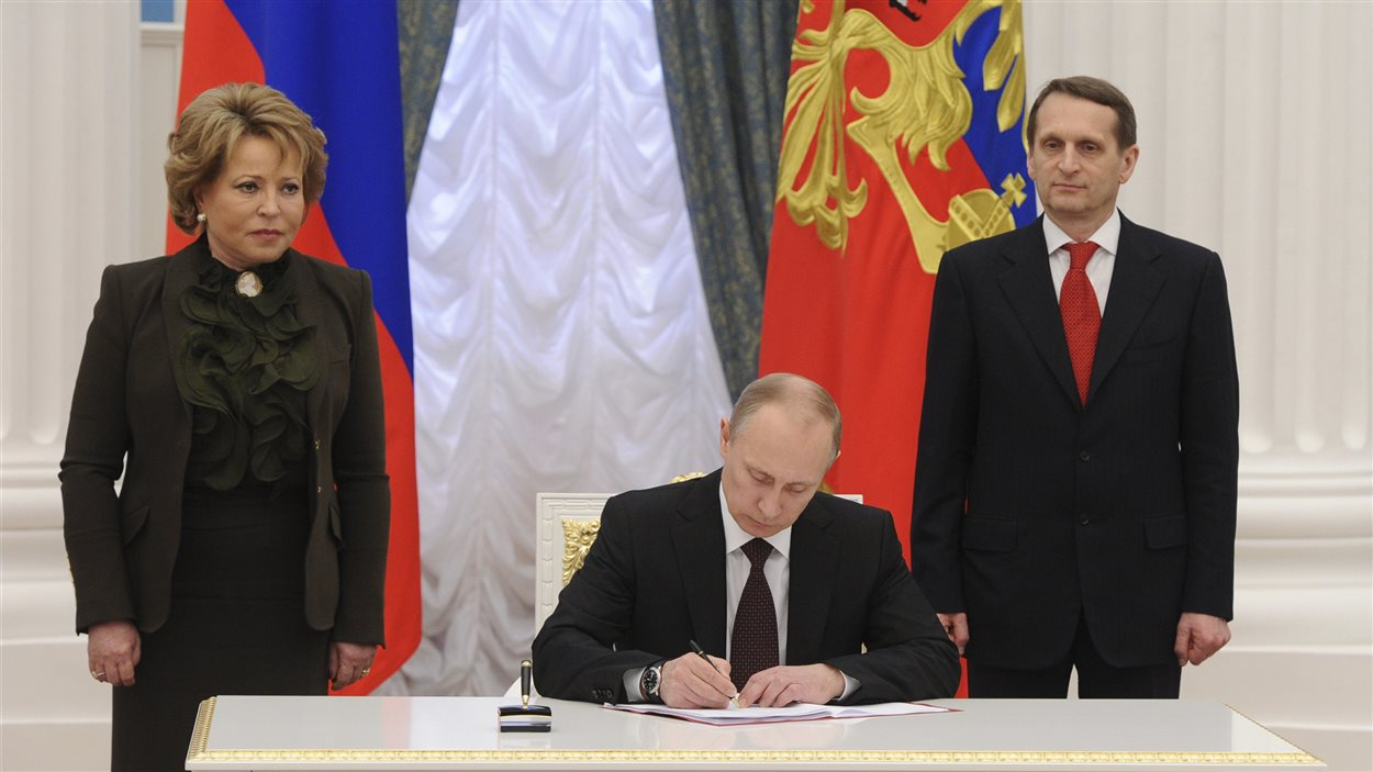 Le présdient russe Vladimir Poutine signe le traité de rattachement de la Crimée à la Russie ainsi que la loi créant deux nouvelles entités administratives russes, la Crimée et la ville portuaire de Sébastopol.