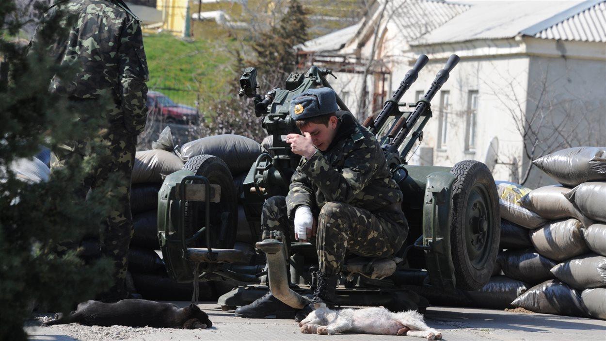 Un soldat ukrainien fume une cigarette à côté d'une mitrailleuse sur la base aérienne de Belbek, près de Sébastopol en Crimée.