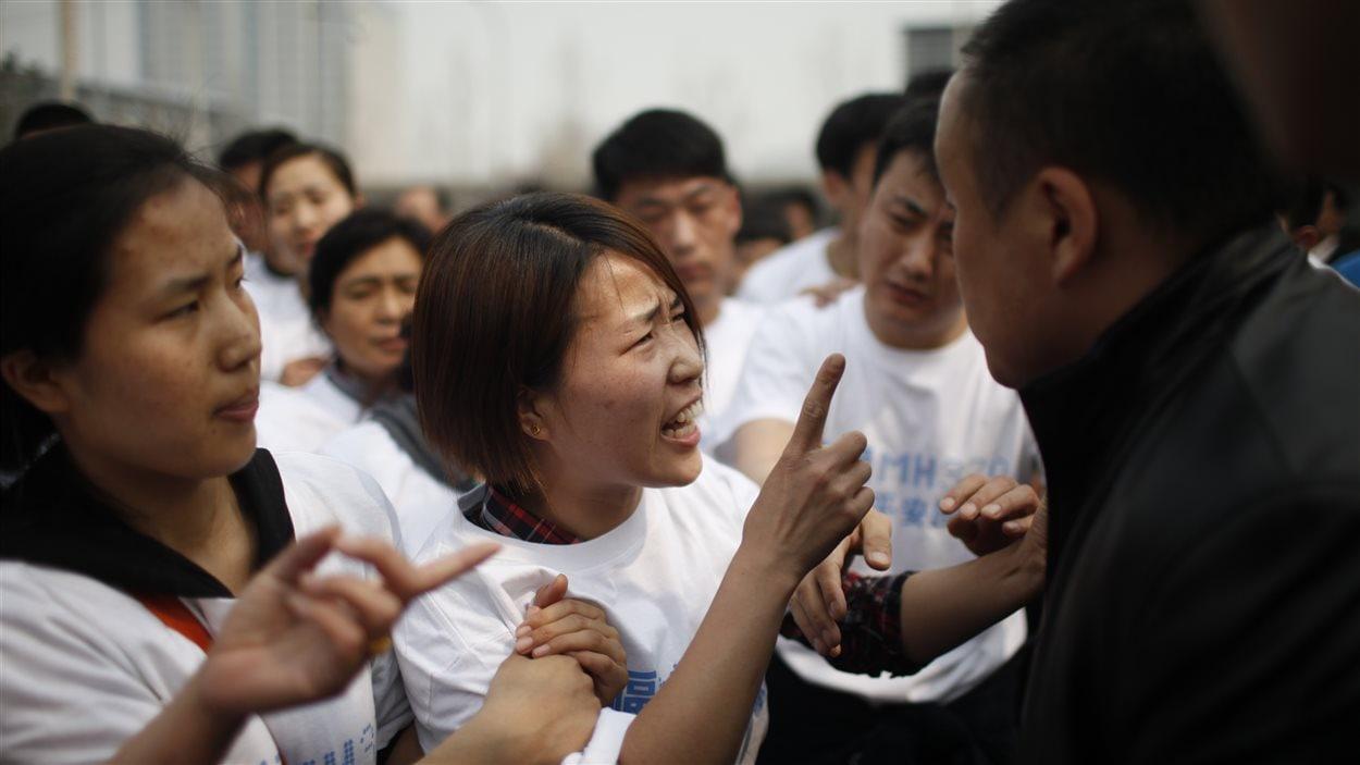 Une proche d'un disparu du vol MH370 en colère, à Pékin.