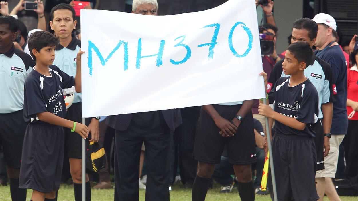 Des enfants ont tenu une bannière en l'honneur des passagers du vol MH370 avant un match de soccer disputé à Kuala Lumpur, en Malaisie.