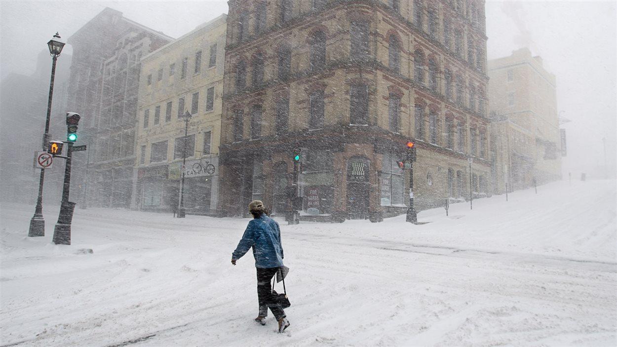 Une passante marche dans les rues désertes de Halifax, en Nouvelle-Écosse.