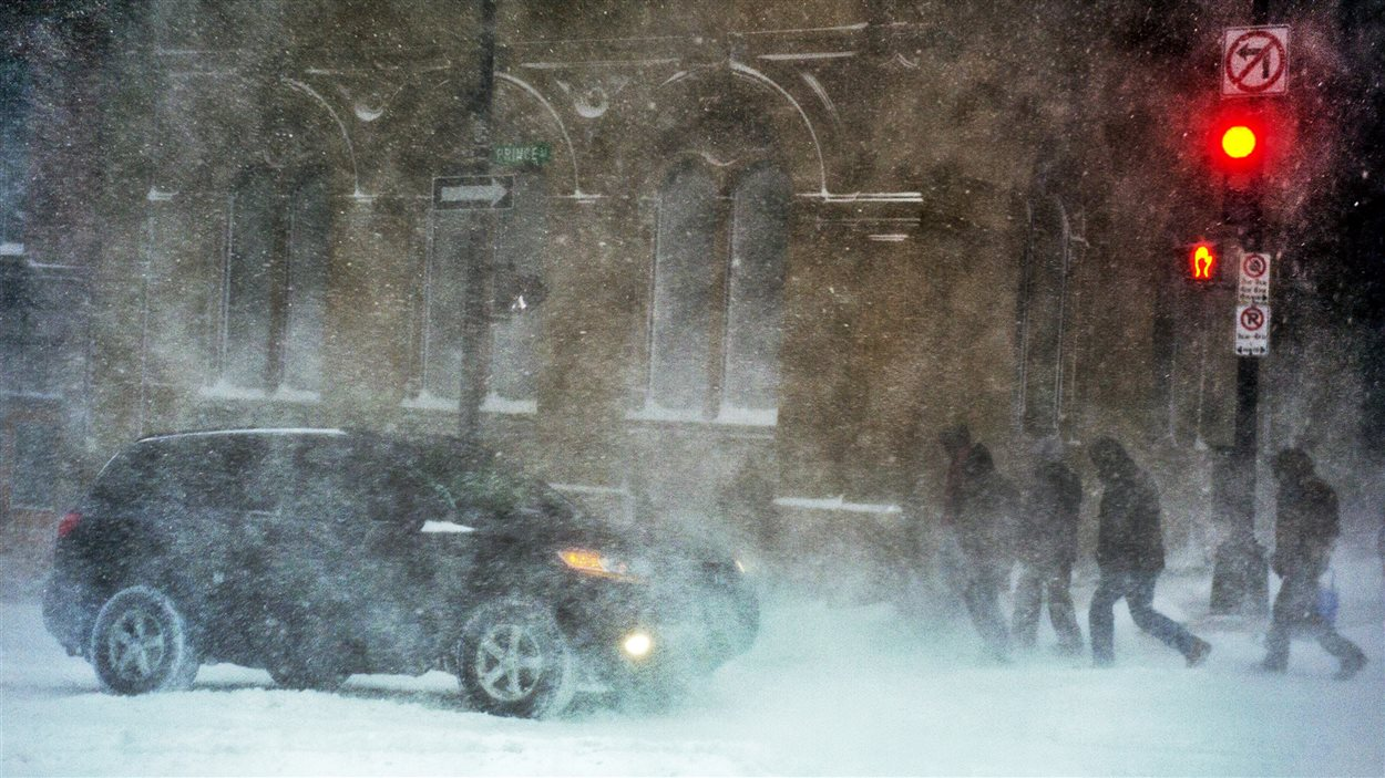 Des piétons affrontent la poudrerie au centre-ville de Halifax.