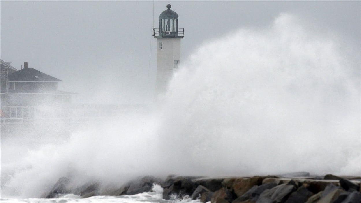 Des vagues surbmergent la jetée sur un rivage du Massachusetts.