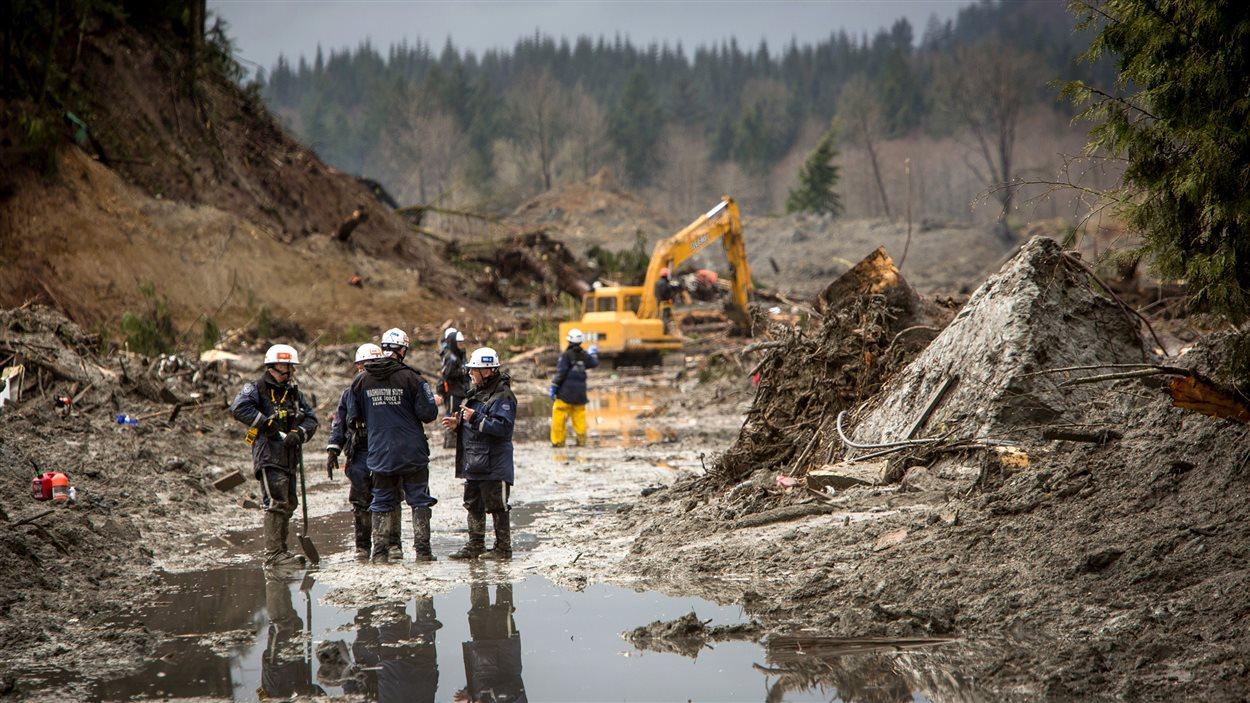 Les sauveteurs ont continué leurs recherches, samedi, dans la boue et les débris laissés par le glissement de terrain, le long de la route 530 près de Darrington.
