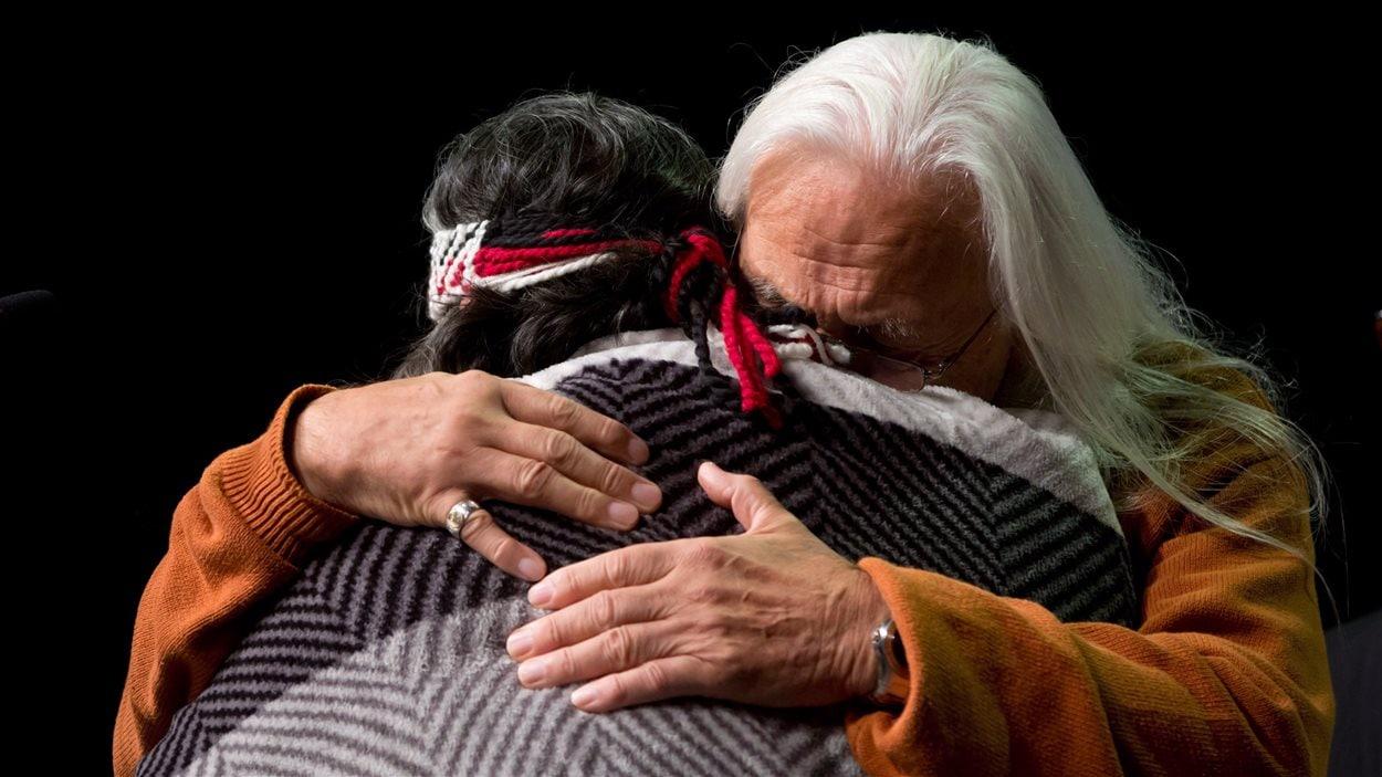 Les survivants Joe George (droite) et Marie George (gauche) s'embrassent pendant un événement de la Commission à Vancouver, le 18 septembre 2013