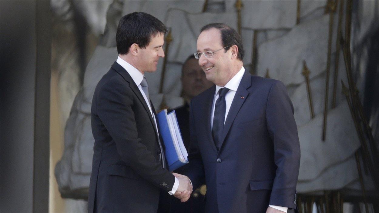 Le président François Hollande (droite) salue son nouveau premier ministre, Manuel Valls (gauche), devant l'Élysée à Paris le 2 avril 2014