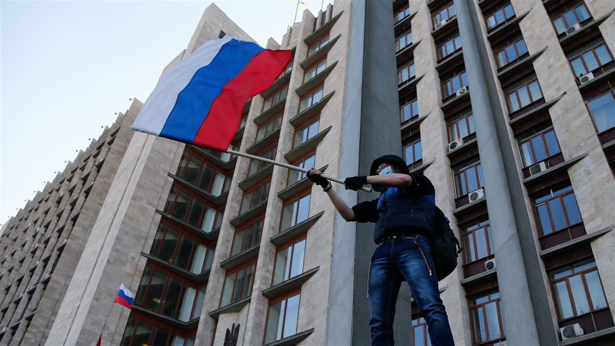 Un militant masqué agite un drapeau russe en face du bâtiment de l'administration régionale de Donetsk, en Ukraine.