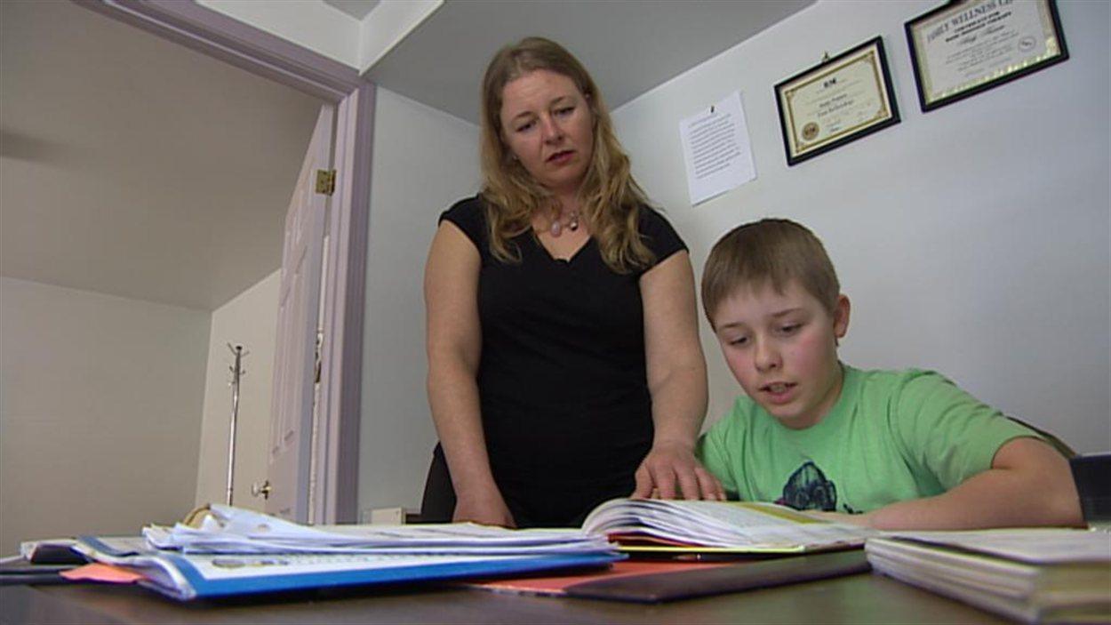 Kim Baul aide son fils, Aidan Walsh, avec ses devoirs, depuis qu'il est suspendu de son école, car il n'est pas vacciné contre la rougeole.
