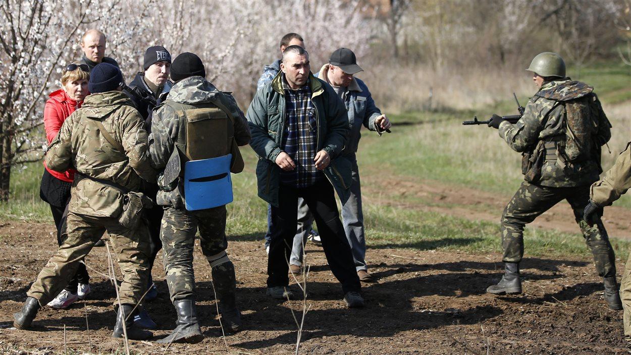 Un soldat ukrainien tient en joue des manifestants prorusses