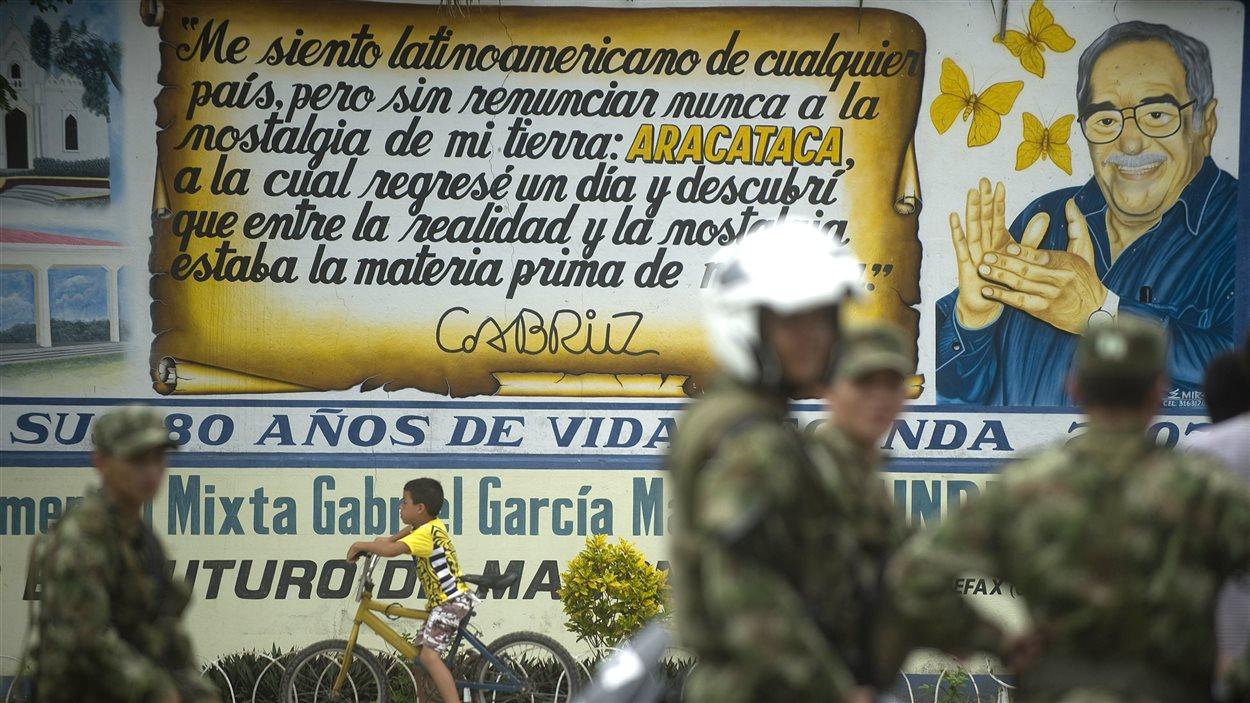 Des soldats se tiennent devant une murale dédiée à l'auteur dans sa ville natale d'Aracataca, en Colombie.