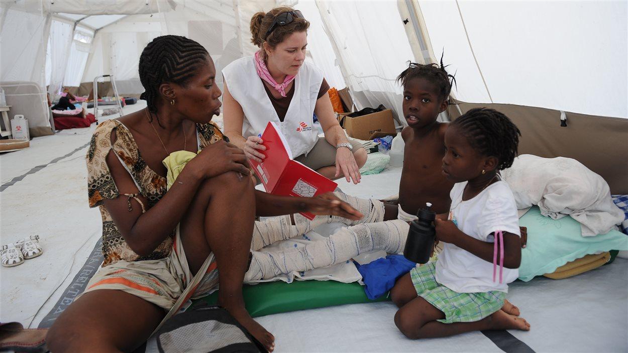 En janvier 2010, à Port-au-Prince, en Haïti, une infirmière de Médecins sans frontières assiste une famille affligée par le tremblement de terre.