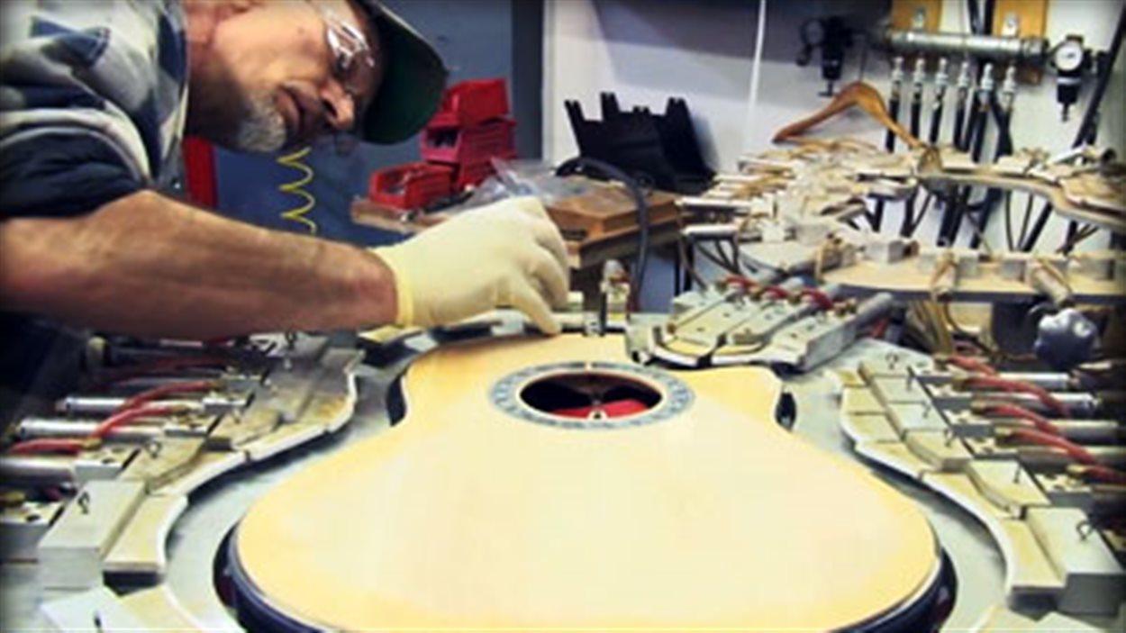 Un ouvrier dans la manufacture de guitares Ovation