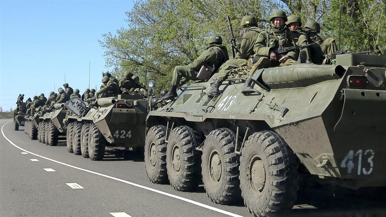 Des chars russes transportent des hommes armés, dans la banlieue de la ville de Belgorod près de la frontière entre la Russie et l'Ukraine.