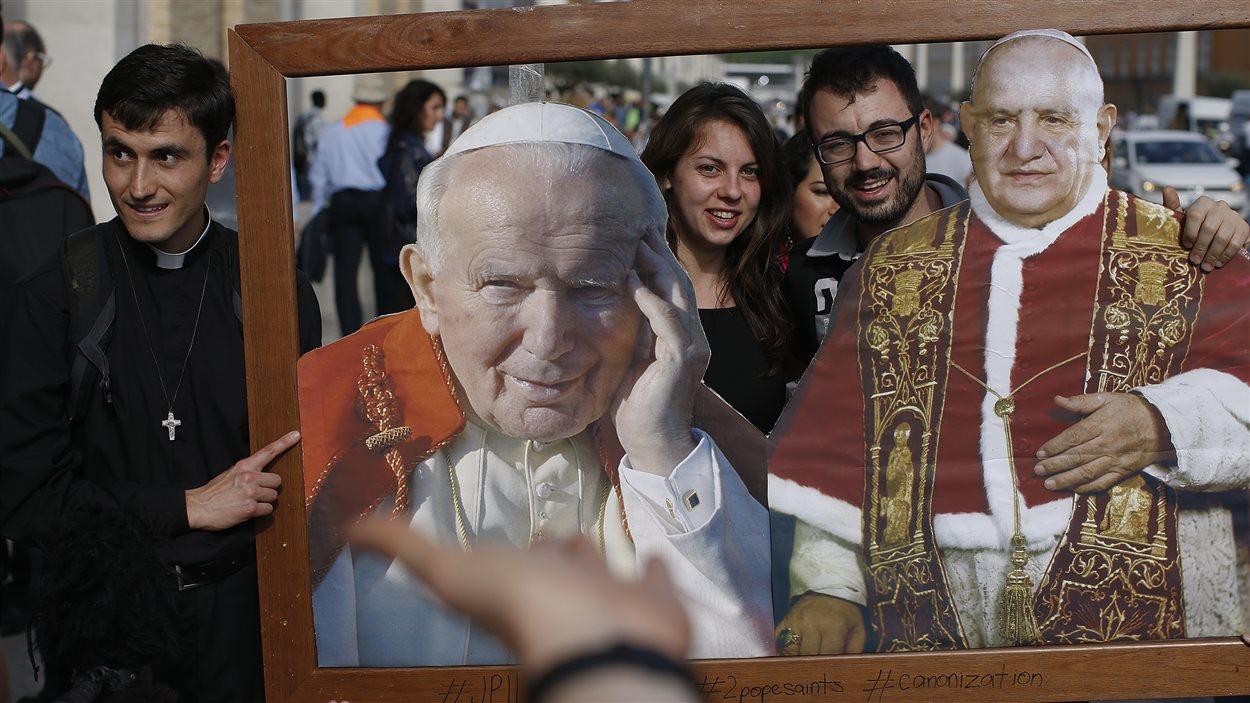 Des touristes prennent des photos à Rome avec les portraits des futurs saints.