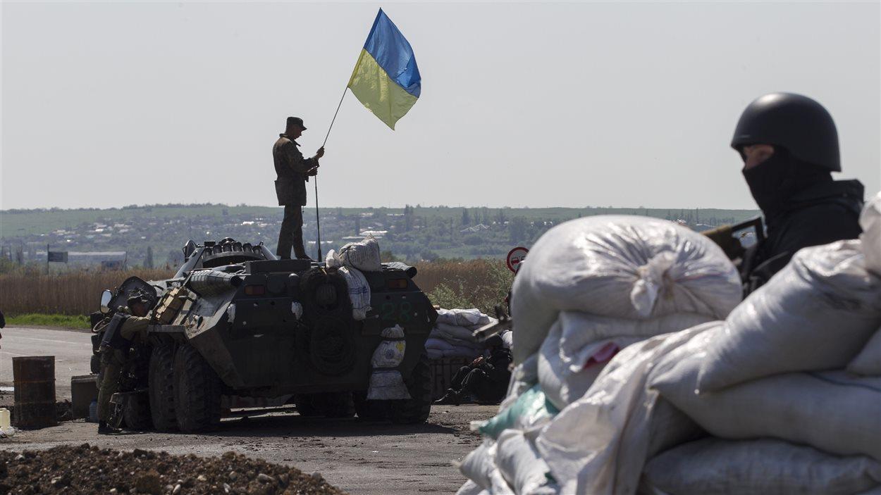 Un soldat accroche un drapeau ukrainien à un poste de contrôle près de la ville de Sloviansk, dans l'est du pays.