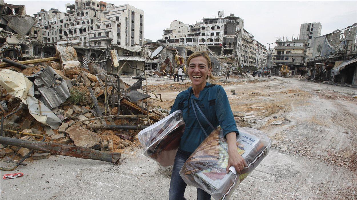 Une résidente de Homs contente d'avoir retrouvé quelques effets personnels dans sa maison détruite.