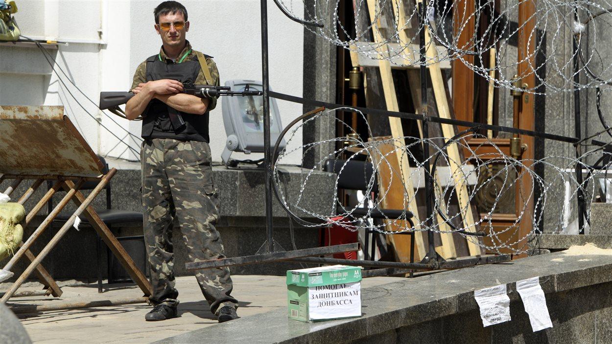 À Louhansk, un milicien prorusse monte la garde devant une boîte destinée aux dons qui financeront notamment le référendum qui sera tenu dimanche.