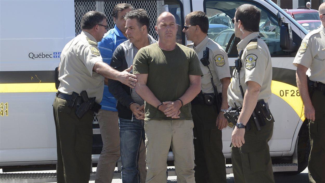 Les trois accusés Thomas Harding (droite), Jean Demaitre (centre) and Richard Labrie (en arrière) sont escortés par la police.