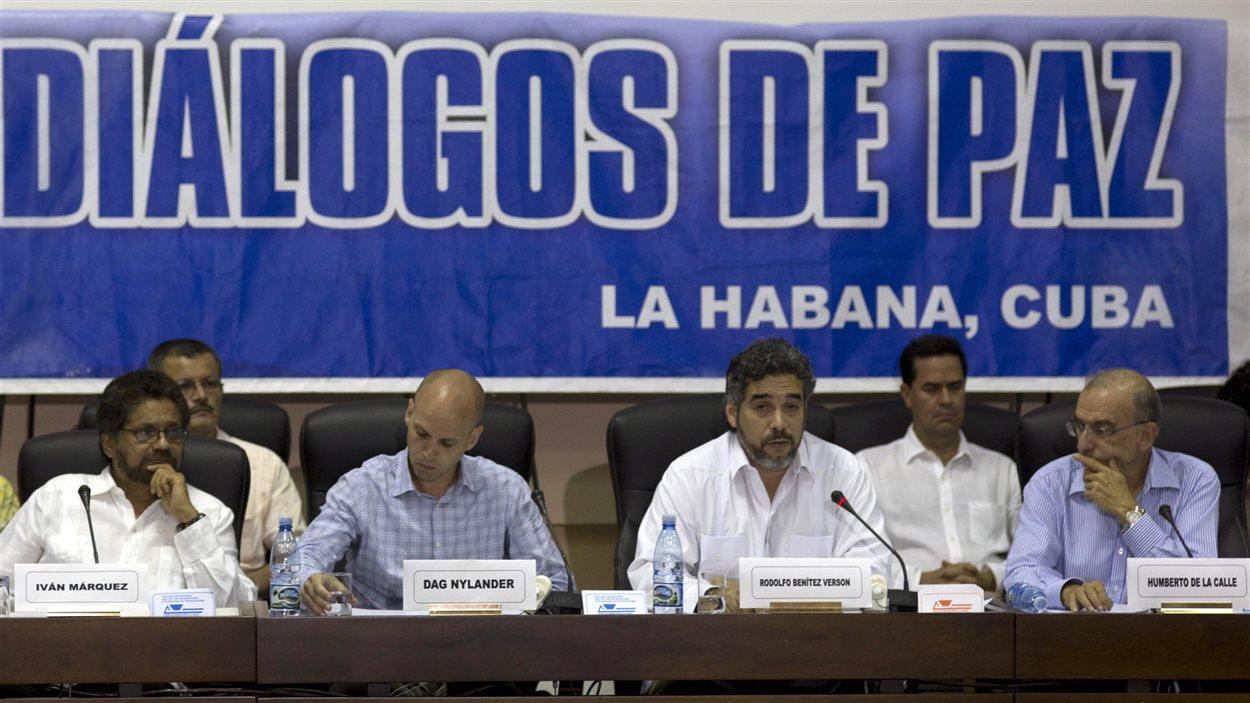 Le négociateur en chef des FARC, Ivan Marquez (gauche) et le négociateur pour le gouvernement colombien, Humberto de la Calle (droite) écoutent le représentant cubain pour les pourparlers de paix, Rodolfo Benitez Verson, qui fait la lecture du texte de l'accord, à La Havane, le 16 mai.