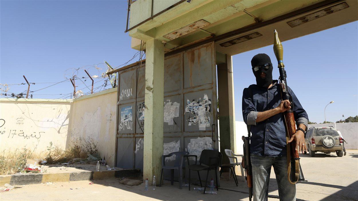 Un milicien libyen se tient devant l'entrée d'un camp d'entraînement le 17 mai, au lendemain d'affrontements mortels avec les autorités