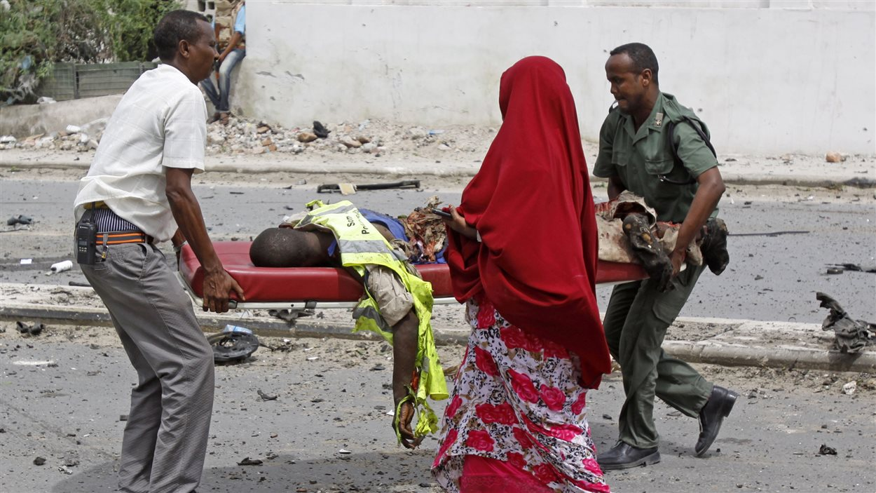 Des soldats transportent un policier blessé lors de l'attentat à Mogadiscio, le 24 mai.