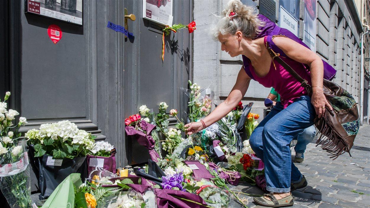 Une femme dépose des fleurs devant le Musée juif de Bruxelles, au lendemain de la fusillade.