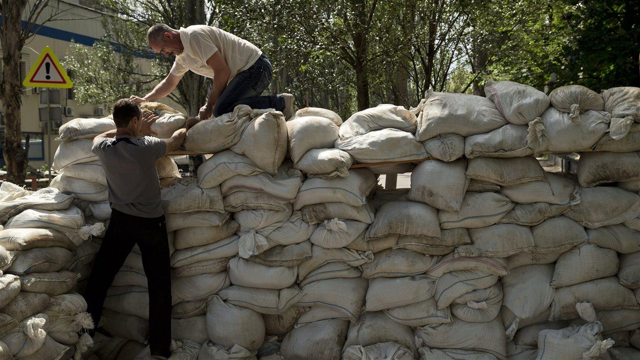 Des gens empilent des sacs de sable pour avoir une position de tir, près de l'aéroport de Donetsk.
