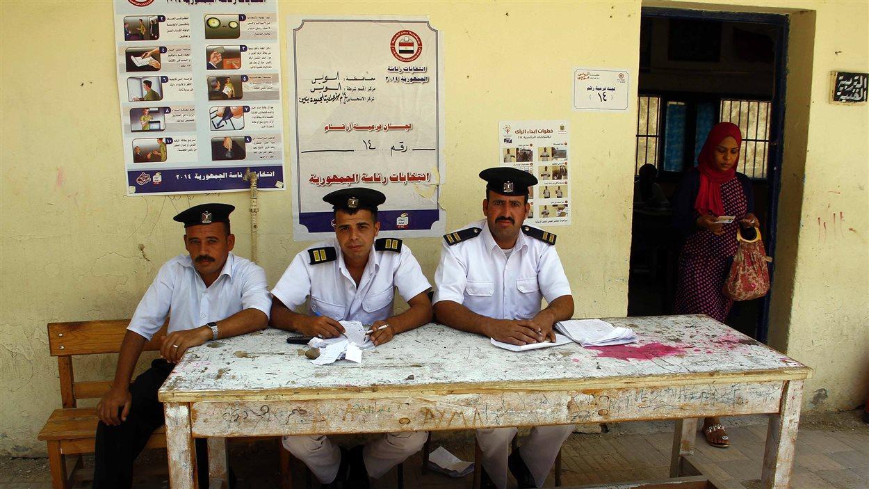 Des policiers égyptiens chargés de vérifier l'identité des électeurs à un bureau de vote du Caire attendent leur prochain client.
