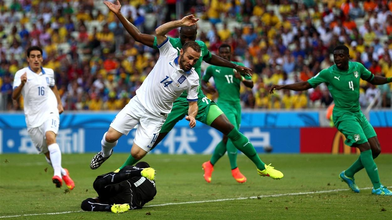Le Grec Dimitris Salpingidis trébuche sur le gardien ivoirien Boubacar Barry en première demie.