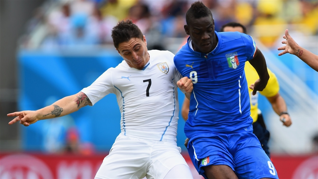 L'Uruguayen Cristian Rodriguez (gauche) et l'Italien Mario Balotelli en pleine lutte pour le ballon.
