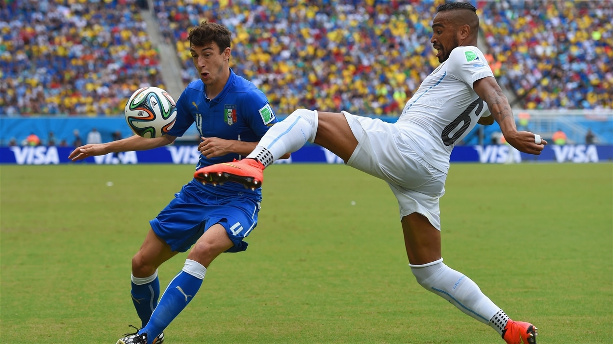 L'Italien Matteo Darmian (gauche) ne peut que regarder l'Uruguayen Alvaro Pereira s'exécuter.