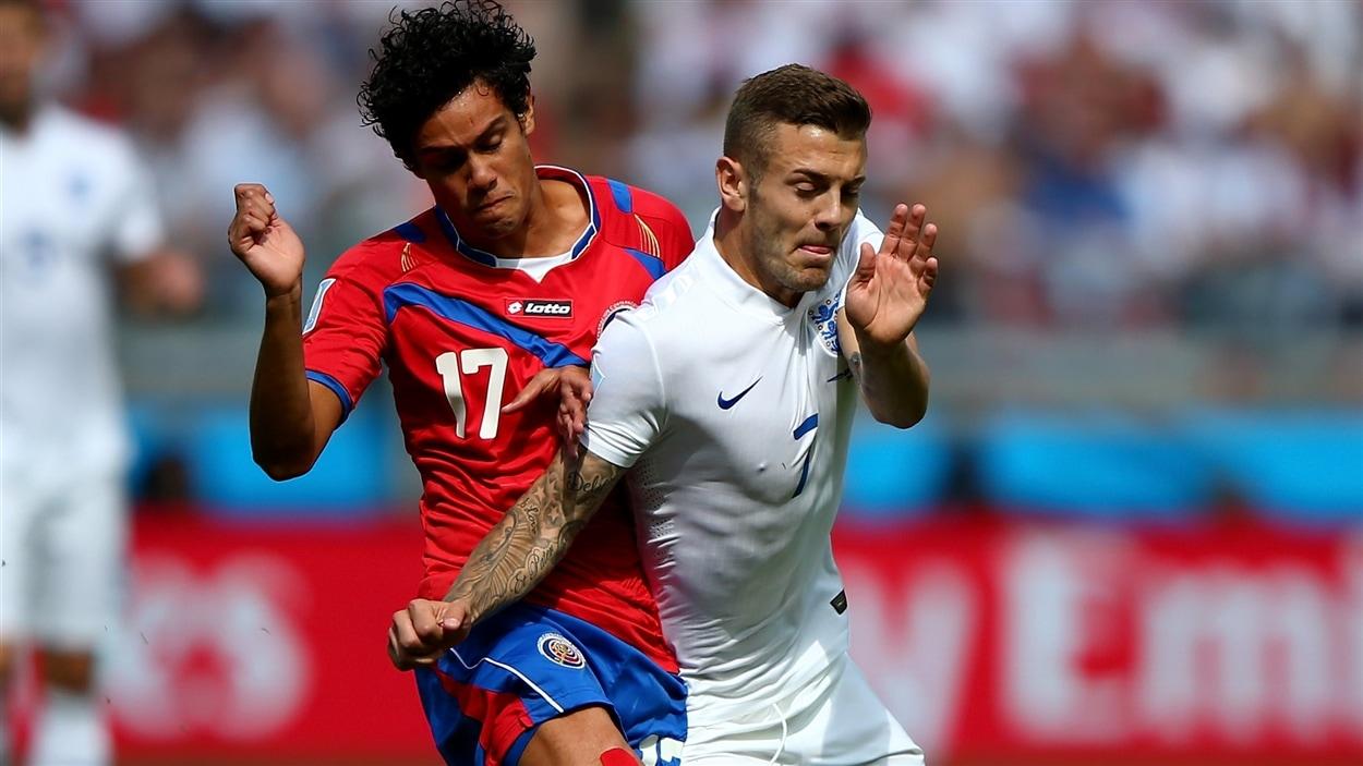 Le Costaricain Yeltsin Tejeda (gauche) et l'Anglais Jack Wilshere triment dur pour prendre possession du ballon.