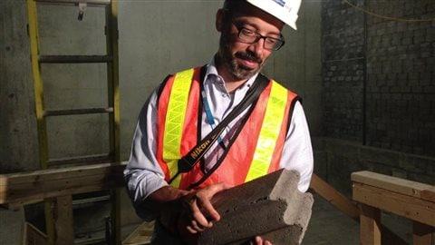 Le Dr David Roberge, chef du département de la radio-oncologie, montre une brique de ciment et de métaux qui compose les murs de la radiothérapie et qui protège de la radioactivité.