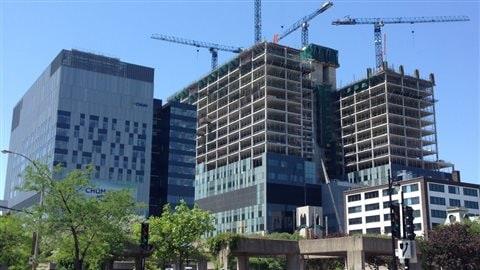 Le CHUM comptera 21 étages et quatre sous-sols. Il y aura des chambres du 8e au 20e étage. À gauche, le centre de recherche, qui a été inauguré à l'automne2013.