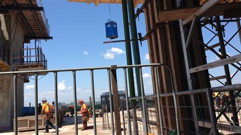 1500 ouvriers travaillent en ce moment sur le chantier. Une telle construction au centre-ville nécessite toute une logistique. Les toilettes, notamment, sont montées sur les étages par des grues.