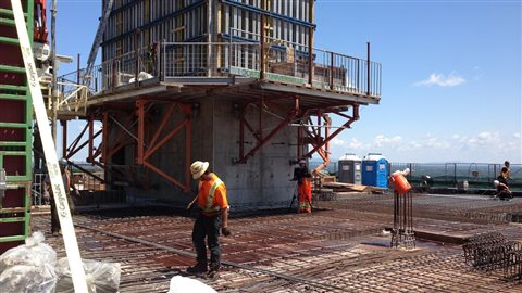 Au 20e étage. Il y en aura un de plus, qui comprendra des salles de mécanique. Pendant que des ouvriers s'affairent à construire la structure, d'autres s'attaquent déjà à la finition intérieure dans les étages du bas.