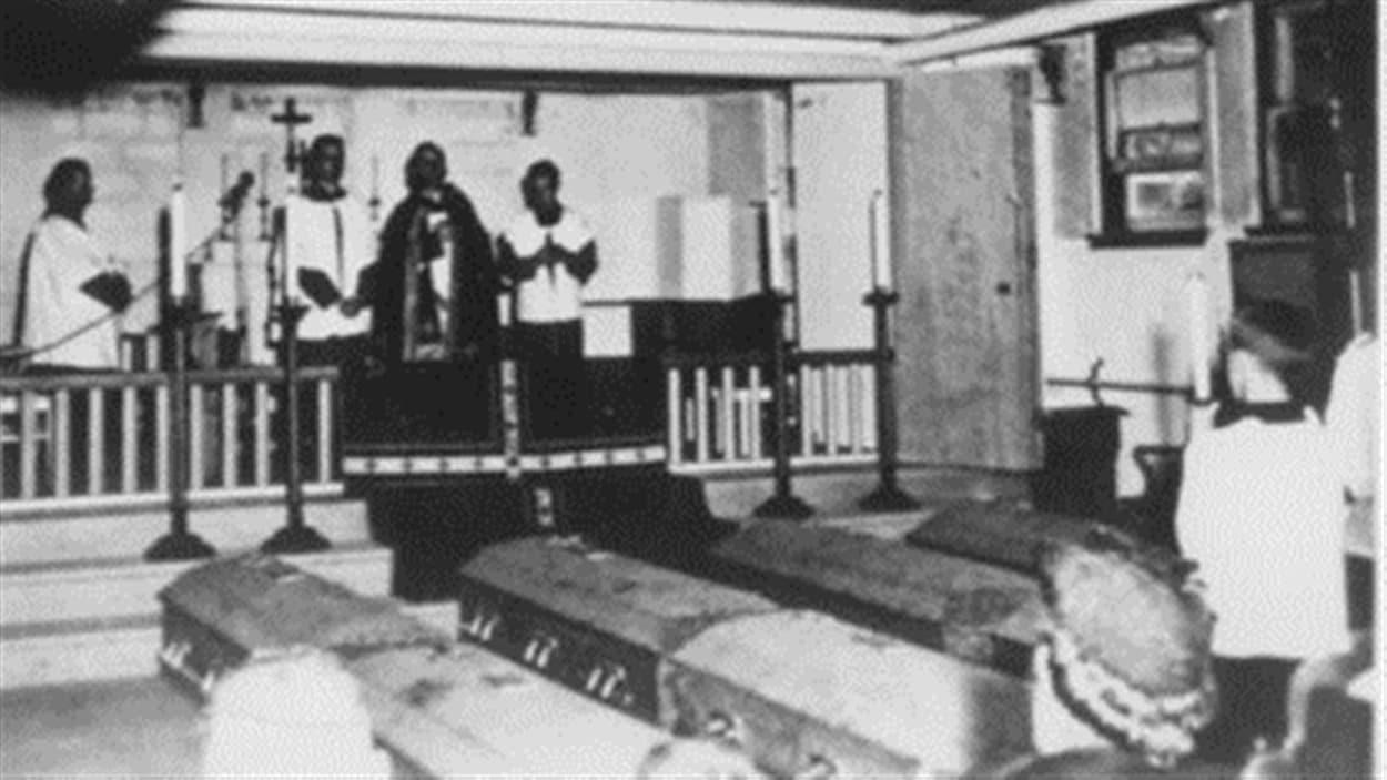 Les citoyens de Malartic prient devant les cercueils à l'intérieur du salon funéraire.