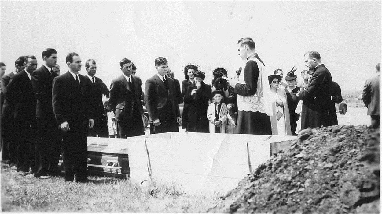 Accompagné du curé Ranger de Dubuisson, l'abbé Gérard Kinlough entame une dernière prière devant un cercueil, épilogue du cérémonial religieux pour ce disparu.