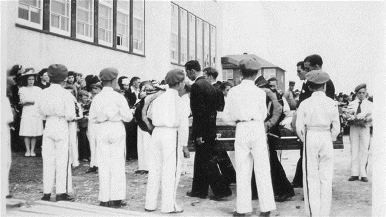 Les membres du Corps de clairons forment une haie sur le passage des porteurs, des pompiers et des membres des familles éprouvées.