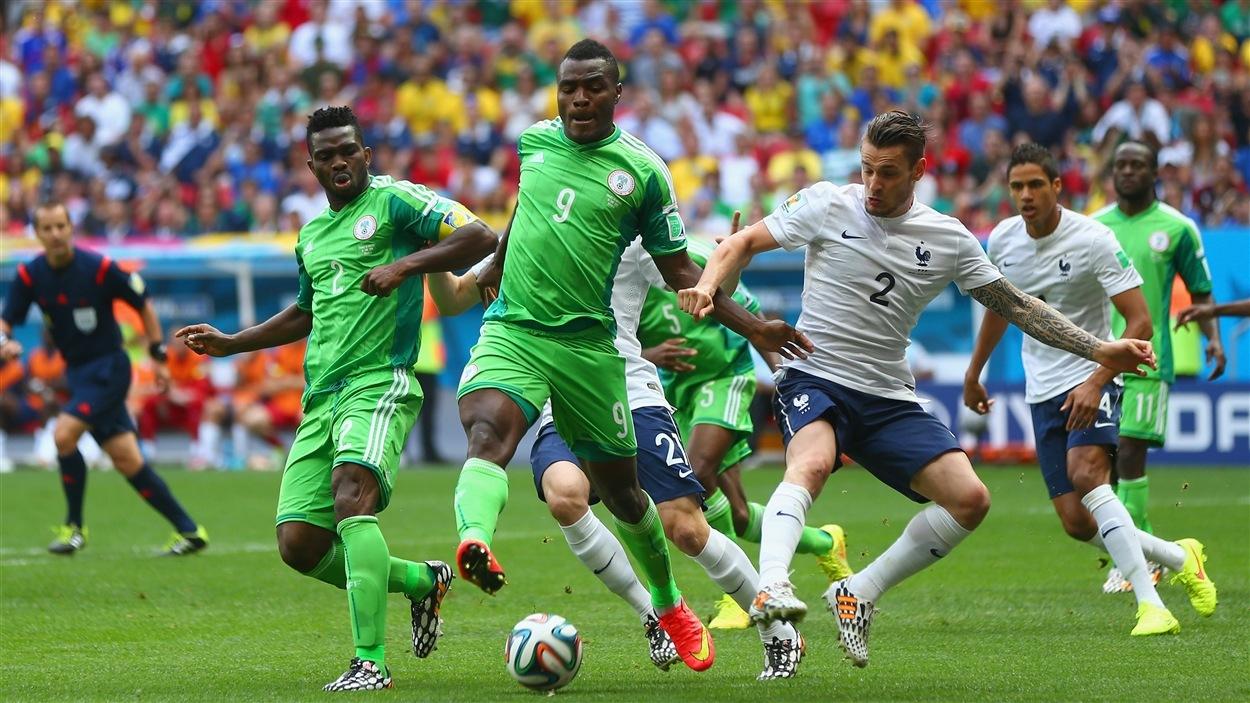 Emmanuel Emenike, du Nigeria, réussit à conserver le ballon devant le Français  Mathieu Debuchy.