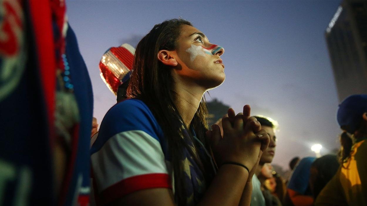 Les yeux rivés sur l'écran géant installé sur la plage de Copacabana, une partisane américaine espère...