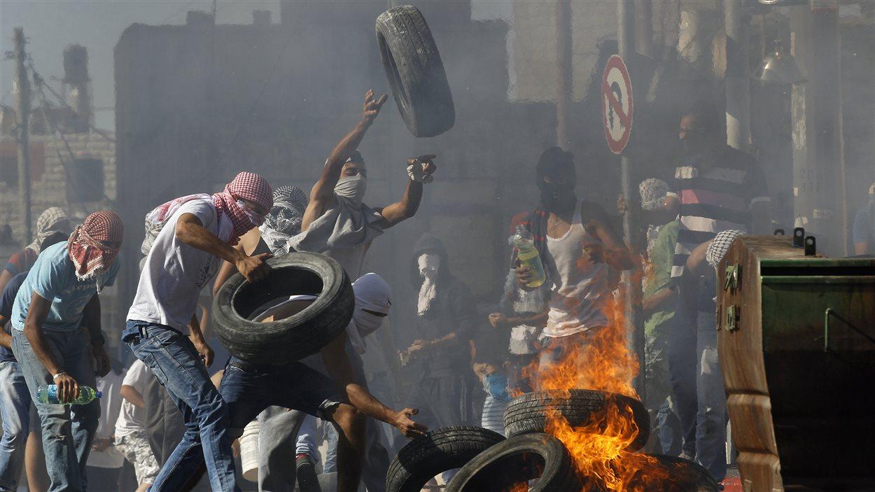 Des manifestants palestiniens enflamment des pneus dans une banlieue de Jérusalem.