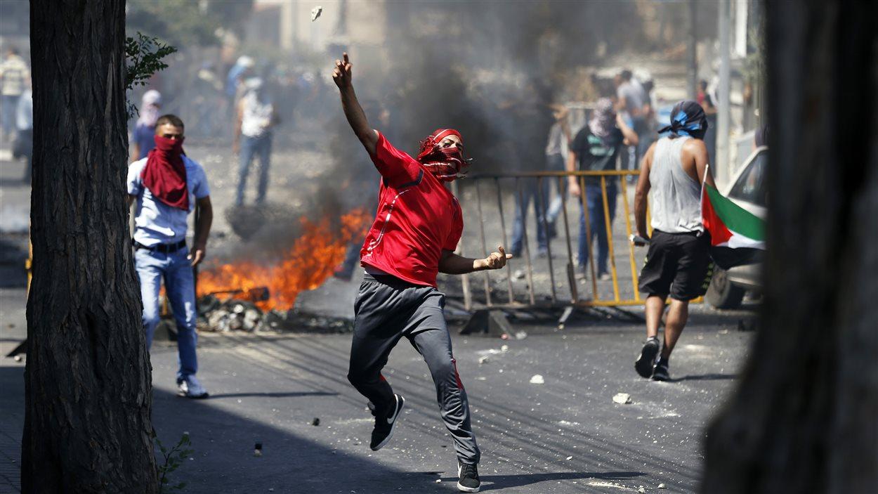 Un Palestinien lance une pierre lors des affrontements avec les forces de l'ordre à Jérusalem-Est, le 4 juillet 2014