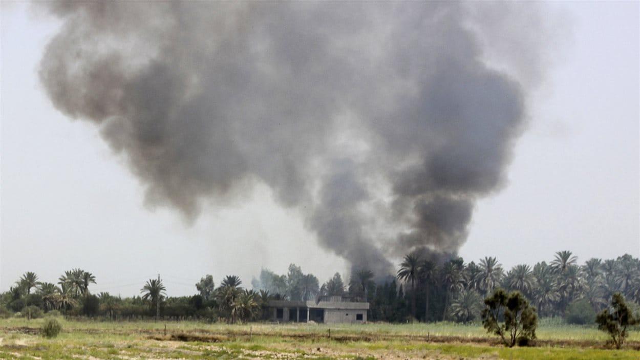 De la fumée se dégage d'un village lors d'un accrochage des forces irakiennes et des insurgés islamistes dans la ville de Dalli Abbass dans la province de Diyala.