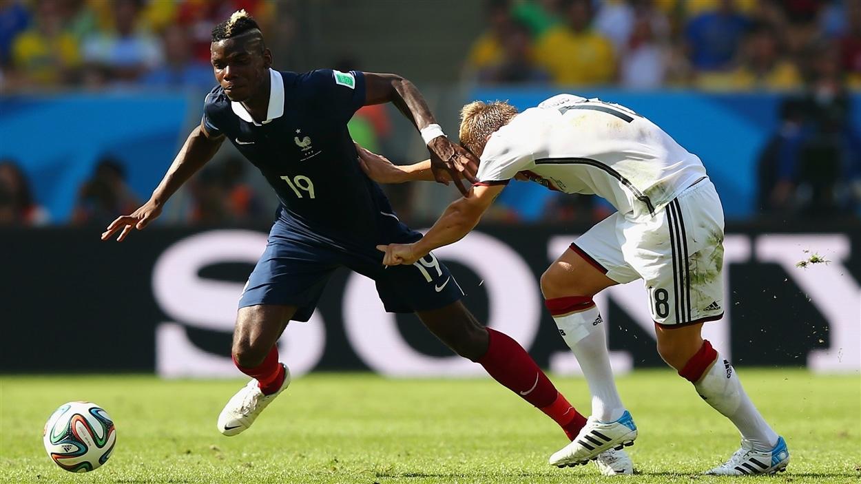 L'Allemand Toni Kroos tente par tous les moyens de ralentir le Français Paul Pogba.