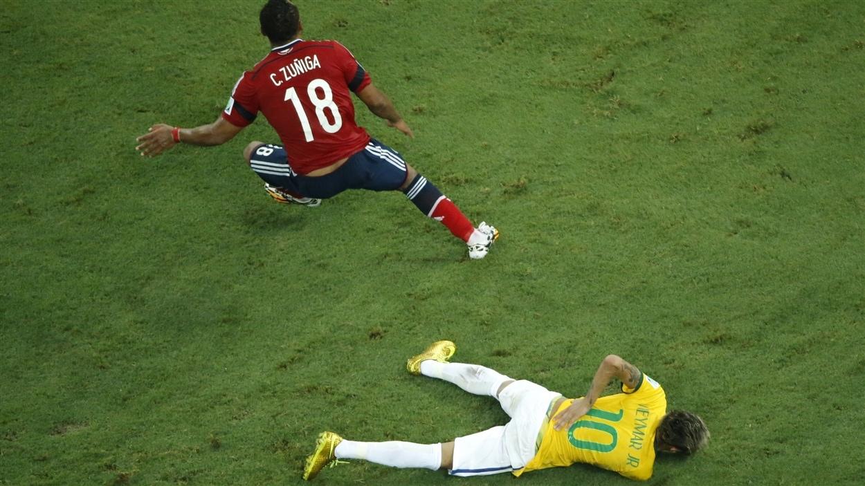 Juan Camilo Zuniga tourne le dos à Neymar, étendu au sol.