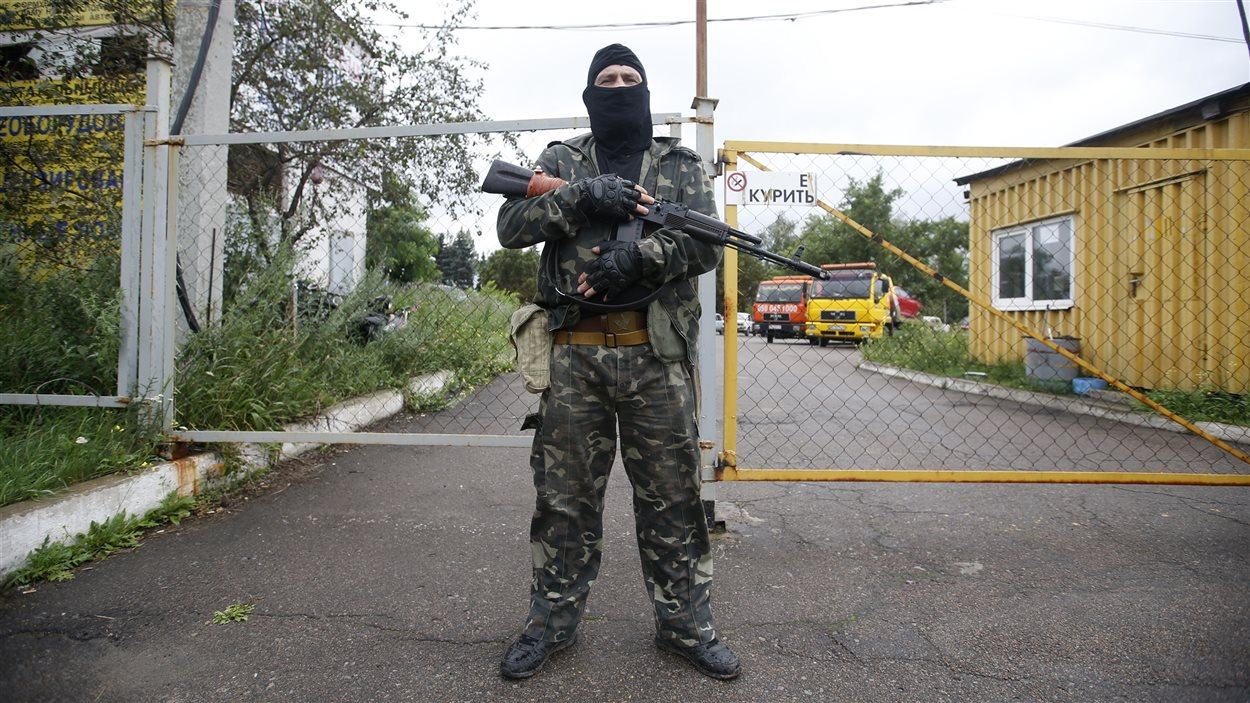 Un insurgé prorusse monte la garde à un poste de contrôle.